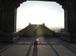 Becky standing in the arch at the highest point overlooking the lower structure roof and the setting sun.
